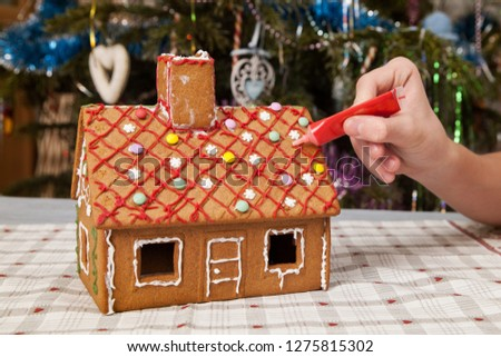 the kid decorates gingerbread house.
