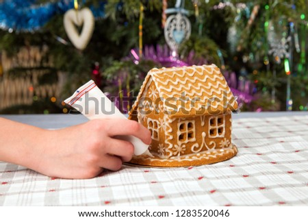 the kid decorates gingerbread house at christmas.