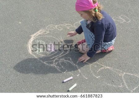 the kid draws mom on asphalt on a summer day. #661887823