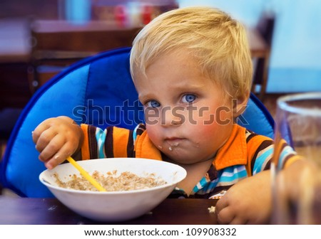 The kid eats porridge
