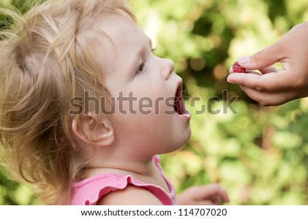 The kid has opened a mouth and to it the hand puts