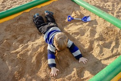 The kid is lying on his stomach in the sand in the city playground.