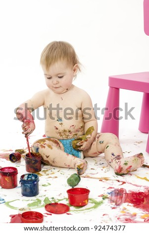 The kid plays with paints a white background