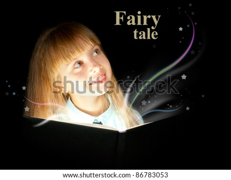 The kid reading a book of fairy tales and dreaming