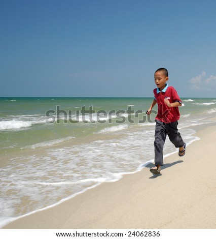 The kid run at the beach during noon