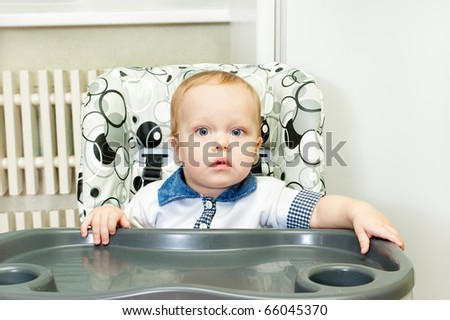 The kid sits in a highchair, interior