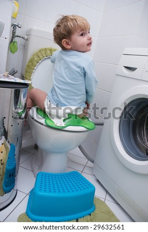 The kid sits on the toilet and laughs
