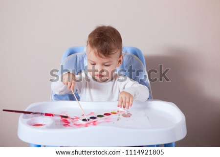 the kid, the future artist, sits at the table and draws for the first time. The child learns to draw a paint brush and draw on paper #1114921805