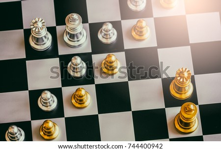 Stock Photo The King in battle chess game stand on chessboard with black isolated background. Business leader concept for market target strategy. Intelligence challenge and business competition success play.