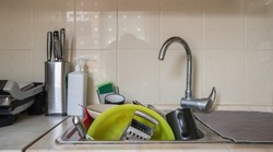 The kitchen utensils in the wash basin need to be washed. A pile of dirty dishes in the kitchen sink. Kitchen utensils need washing. Homework concept