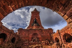 The Kyffhäuser Monument on a sunny day with clouds and blue sky. Bricks in the arch and stones with a statue in Thuringia and southern Harz. Historic building of Kaiser Wilhelm