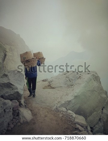 The laborer carries a sulfer cube up from the crater to sell it. #718870660