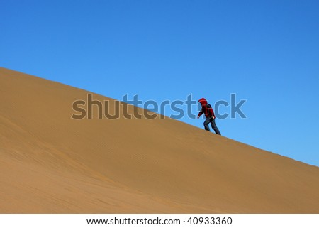 The lady in red is ascending the sand hill in Ba Dan Ji Lin desert, Inner Mongolia, China