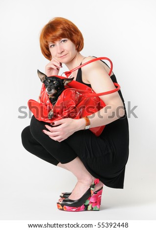 The lady with the small dog in a red bag