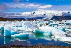 The lagoon Jokulsaurloun in Skaftafell Park. Iceland. Cold day in July. White and blue icebergs and ice floes reflected in the water. The concept of extreme, northern and photo tourism