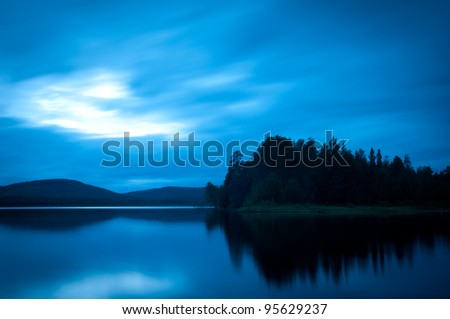 the lake after sunset and is reflected in the water timber