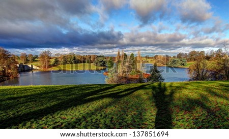 The lake in Blenheim Palace, blue sky with cloudy, peaceful lake and the shadows of trees combined that peaceful landscape. It is a HDR photo. - stock photo