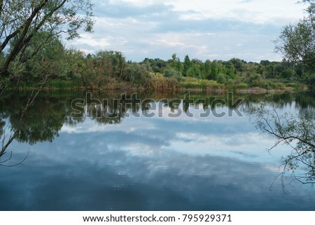 The lake is at sunset. The smooth surface of the pond through the green foliage of the trees. Summer vacation. Protection of the environment. Ecology and the village.