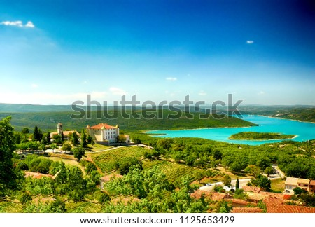 The lake Lac de Sainte-Croix Lake has clear cyan water. The Verdon River flows from the Verdon Canyon. There is a castle above the lake and vineyards around. It is situated in France in Europe.