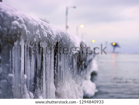 The lakeshore of Lake Michigan is frozen with icicles and frozen snow in the city of Chicago.