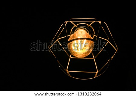 The lamp barely shines in the dark room. Vintage light bulb background ,Warm light bulb, close up of filaments inside