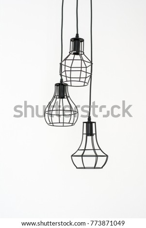 The lamp hangs down from the ceiling on a white floor., Old lamp hanging down from the ceiling in front of concrete background,Modern style light bulb lamp on white background.