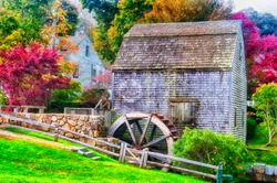 The landmark Dexter Grist Mill and water wheel in sandwich massachusetts in new england during autumn.