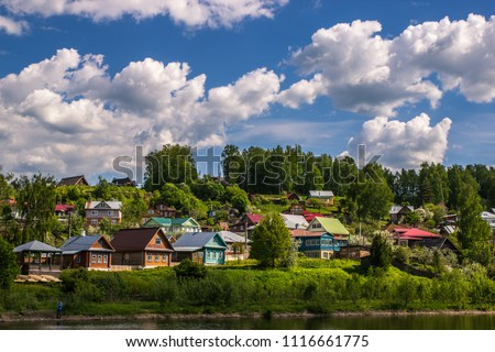 the landscape of a Russian village in summer with colorful houses and a blue sky with huge white clouds, a rustic background