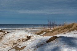 The landscape of the coastal strip of the Baltic Sea in early spring, the last snow and sparse vegetation on the sand against the background of the sea with grayish ice and cloudy sky.