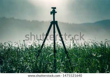 The landscape photo was dawning at dawn. On a green meadow stands a Tripod against the background of the forest and mountains landscape, Carpathian Ukraine. Sunrise.