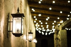The lane between the old houses is lit by a vintage lantern and garlands