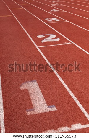 The lanes on a red athletic running track - stock photo