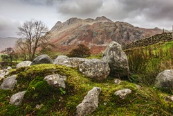 The Langdale Pikes rising beyond a rocky outcrop.