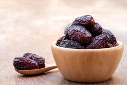 The large date fruits (Medjool) in cups and wooden spoons on a cement with blurred background.