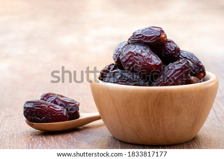 The large date fruits (Medjool) in cups and wooden spoons on a cement with blurred background. Foto stock ©