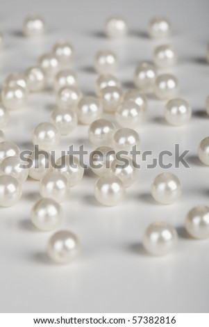 The large pearls are scattered on a grey surface
