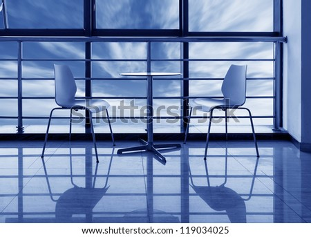 The large windows of the office, the round table and chairs.