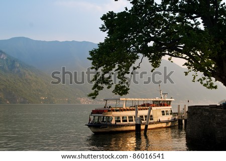 The last ferry docking at Lake Como in the afternoon sun - stock photo