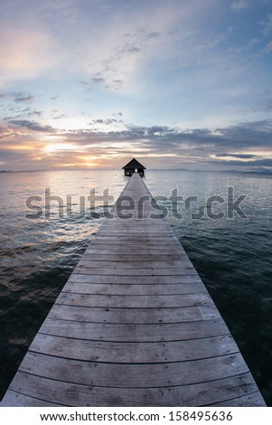 The last light of day falls on a long pier that stretches towards the horizon. This resort pier is on a remote tropical island in eastern Indonesia. #158495636