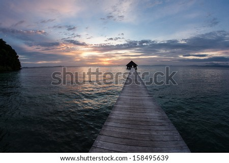 The last light of day falls on a long pier that stretches towards the horizon. This resort pier is on a remote tropical island in eastern Indonesia. #158495639