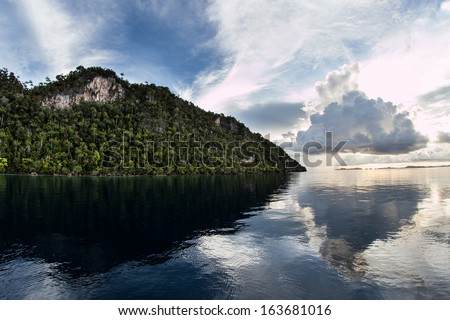 The last light of day illuminates low clouds near the horizon in Raja Ampat, Indonesia. This region is famous for its marine biological diversity and excellent scuba diving. #163681016