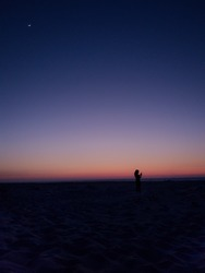 The last moments of sunlight after sunset in the beach with a silhouette of a girl standing alone.