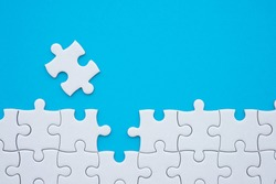 The last piece of jigsaw puzzle to complete task on blue background. Business strategy teamwork, problem solving concept. Teamwork is collaborative effort of team to achieve goal or complete mission.