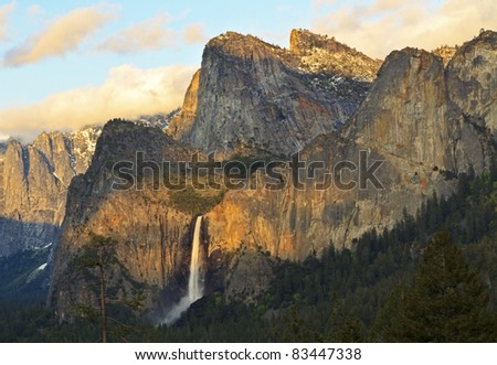 The last rays of sunset splash Cathedral Rocks around Bridalveil Falls in Yosemite National Park, California