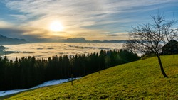 the last sunbeams over the Swiss mountains and the Valley of Rhein. Clouds of veil come from the mountains and create an impressive atmosphere with a circle of Halo. dust and fog lies in the valley