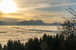 the last sunbeams over the Swiss mountains and the Valley of Rhein. Clouds of veil come from the mountains and create an impressive atmosphere with a wave of fog. dust and fog lies in the valley