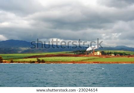 The last working sugar mill on the island of Kauai, Hawaii, under threatening clouds