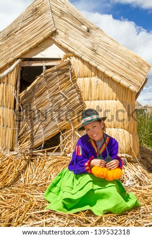 the latin woman in national clothes and totora Hut. Peru. south america