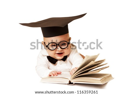 The laughing small child in the academic cap and with the book