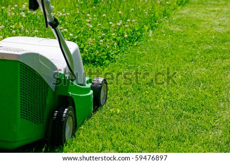 The Lawn mower in the yard on the grass